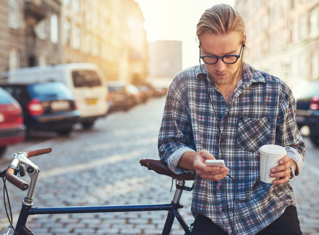 Outdoor portrait of modern young man with mobile phone in the street, sitting on bike