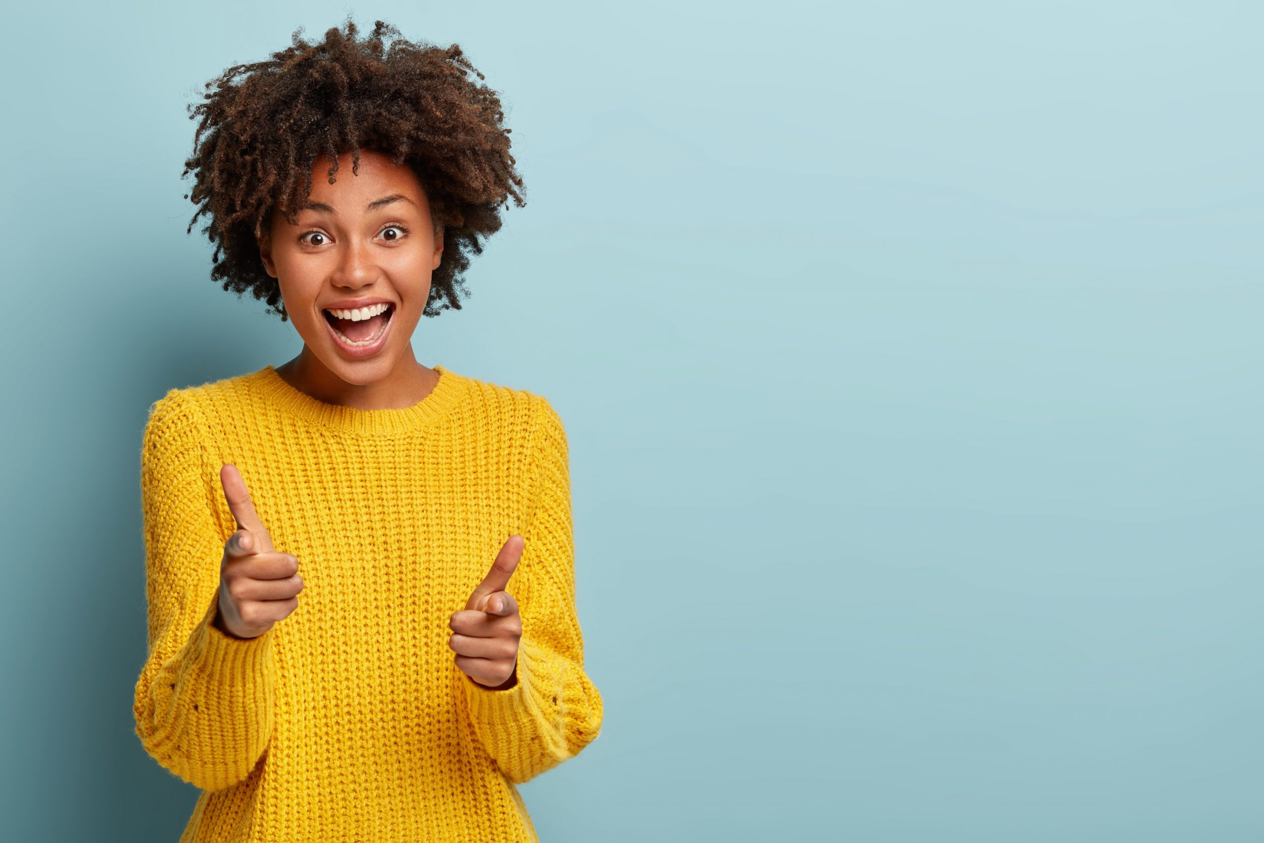 Outgoing carefree woman makes finger pistols, points directly at camera with positive expression, says I choose you, wears casual outfit, stands over blue wall with blank space area. You are my type